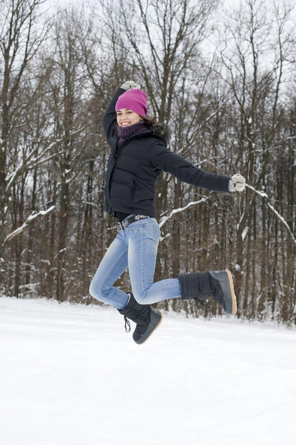 La giovane donna che felice il brunette salta su neve immagini stock libere da diritti