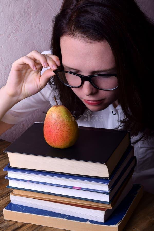 La giovane donna che indossa i vetri sta esaminando la pera fotografia stock libera da diritti