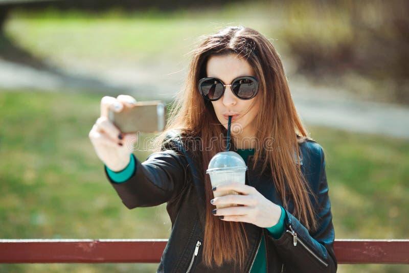 La giovane donna che per mezzo di un telefono fa il selfie immagini stock libere da diritti