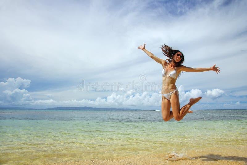 La giovane donna che salta alla spiaggia sull'isola di Taveuni, Figi fotografia stock libera da diritti
