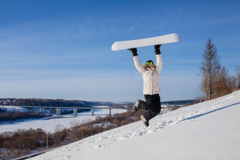 La giovane donna che salta con il suo snowboard immagine stock