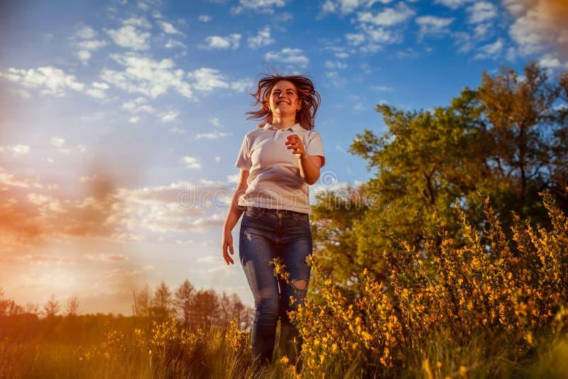 La giovane donna che salta, corrente e divertentesi nel giacimento di primavera al tramonto La ragazza felice e libera si rilassa fotografia stock libera da diritti