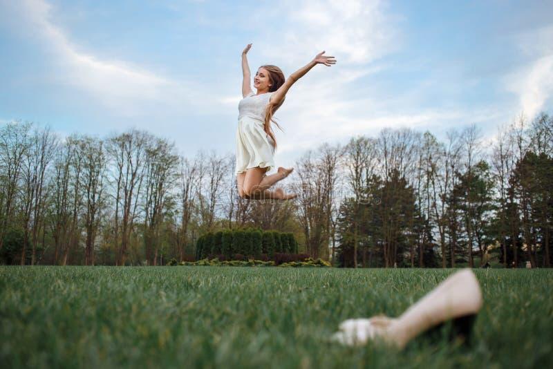 La giovane donna che salta a piedi nudi sul prato verde Libertà e salute nel concetto di megapolice immagine stock