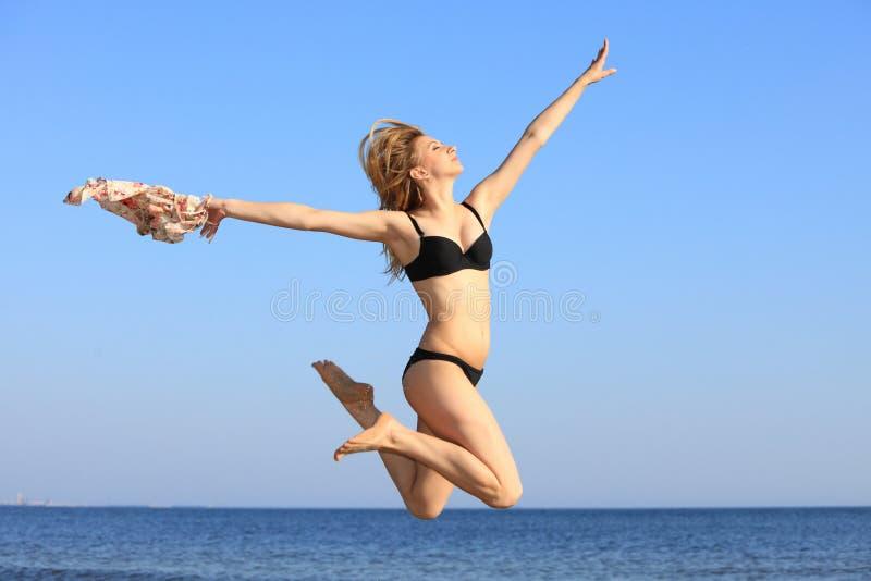 La giovane donna che salta sulla ragazza sportiva adatta della spiaggia fotografia stock libera da diritti