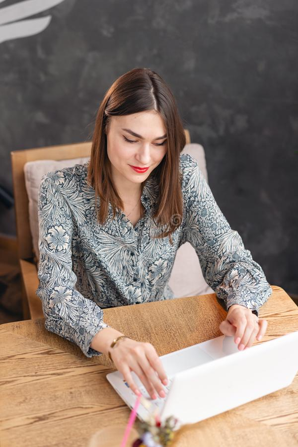 La giovane donna che scrive sulla tastiera, chiacchierante, mantiene un blog Lavoro delle free lance su netbook nel coworking mod fotografia stock libera da diritti