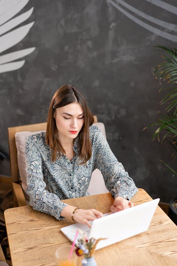 La giovane donna che scrive sulla tastiera, chiacchierante, mantiene un blog Lavoro delle free lance su netbook nel coworking mod fotografia stock