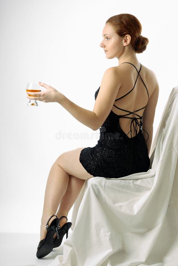 La giovane donna che si siede con il bicchiere di vino, metà-gira fotografia stock libera da diritti