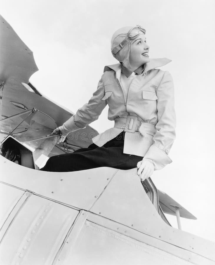 La giovane donna che si siede sopra un biplano con fa i gargarismi e cappello (tutte le persone rappresentate non sono vivente pi immagini stock libere da diritti