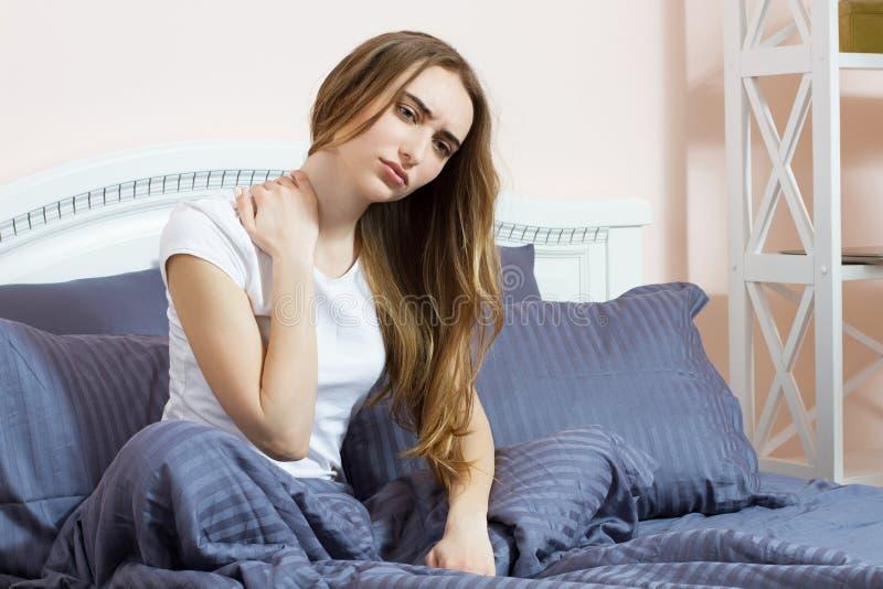 La giovane donna che si siede sul letto con dolore in collo di mattina, soffre la ragazza - materasso scomodo immagine stock libera da diritti