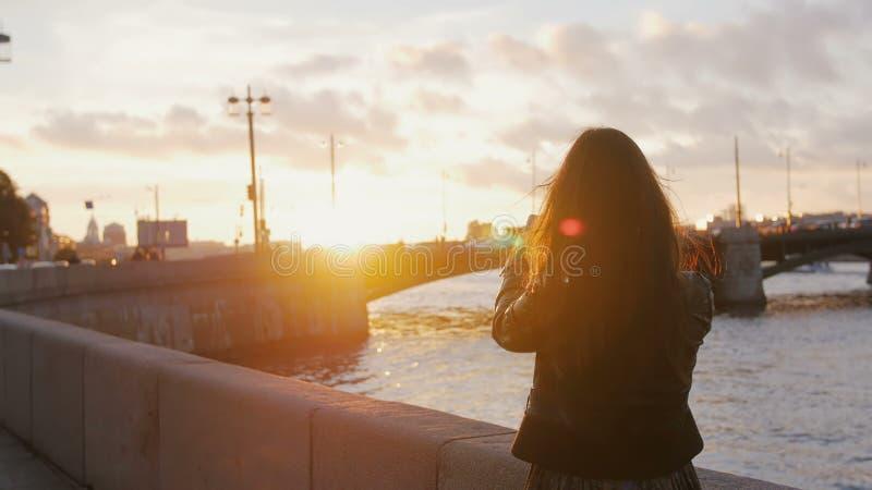La giovane donna che sta sull'argine fa sulla foto dello smartphone del ponte nei raggi luminosi del tramonto 4K fotografia stock libera da diritti
