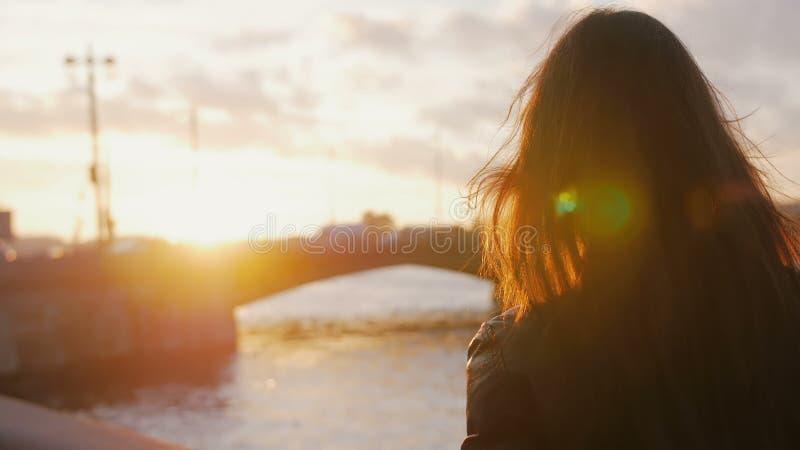 La giovane donna che sta sull'argine fa sulla foto dello smartphone del ponte nei raggi luminosi del tramonto 4K fotografia stock