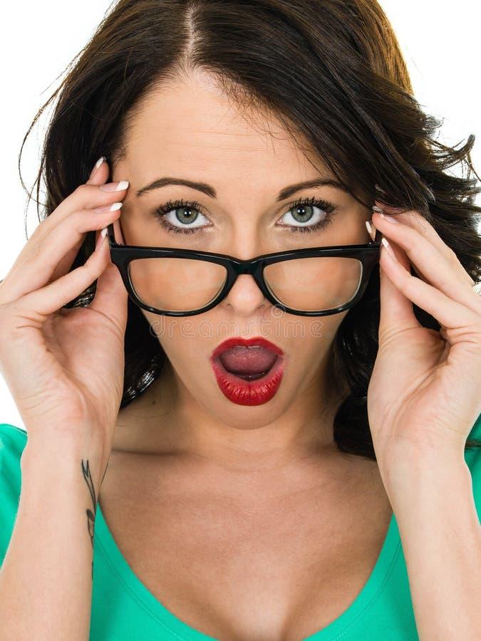 La giovane donna colpita che esamina i suoi vetri con la sua bocca si apre fotografia stock