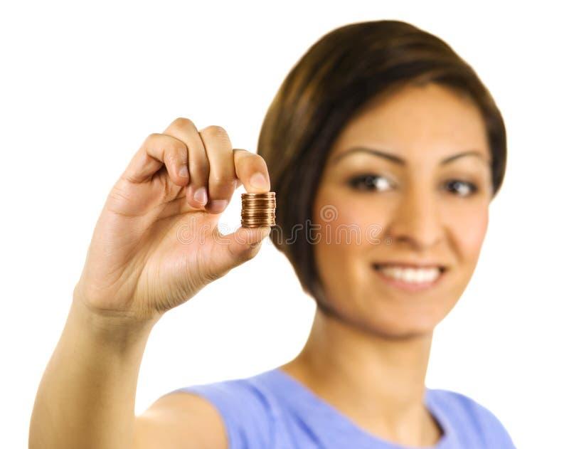 La giovane donna comprime una pila di penny. fotografie stock libere da diritti