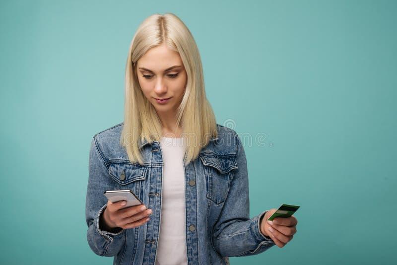 La giovane donna con la carta di credito e lo smartphone effettua il pagamento online dell'acquisto fotografia stock