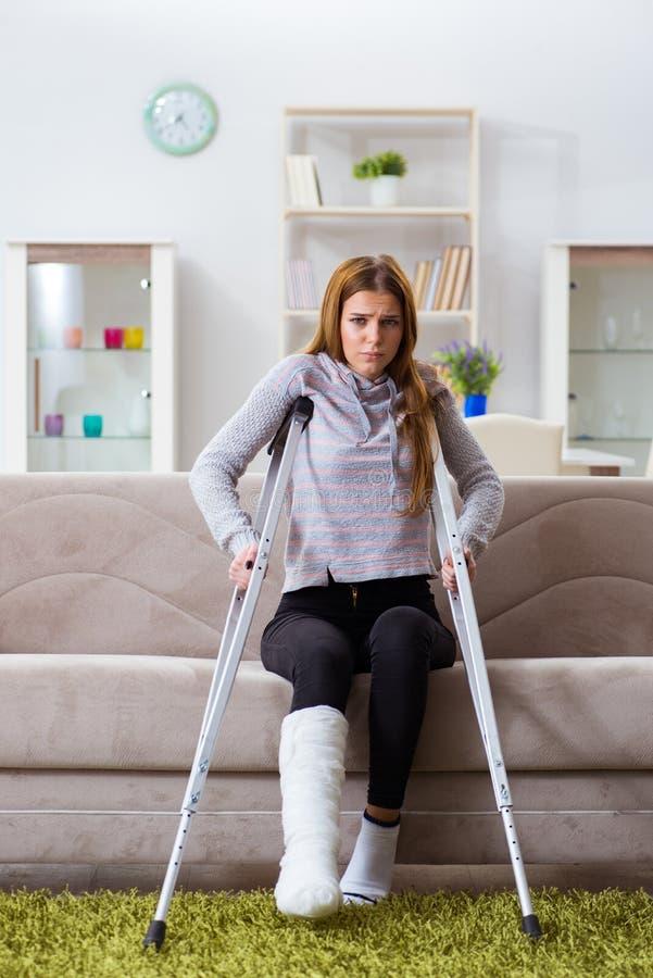 La giovane donna con la gamba rotta a casa immagine stock libera da diritti