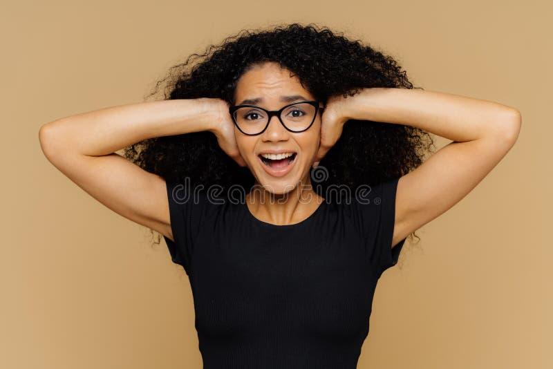 La giovane donna con i capelli ricci di afro copre le orecchie, grida come richieste è calma, smussa il rumore del supporto, tien immagini stock libere da diritti