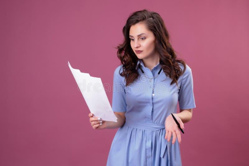 La giovane donna con i punti all'fogli di carta, tiene una penna fotografie stock