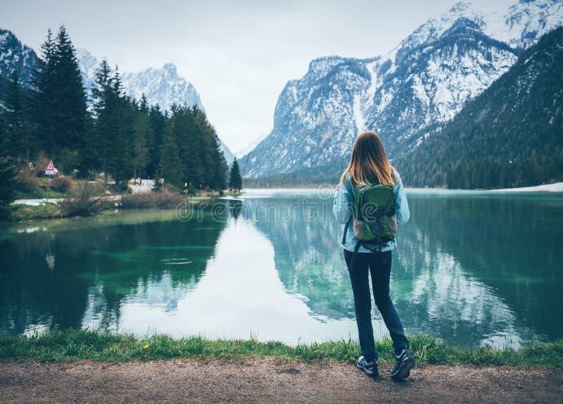 La giovane donna con lo zaino sta stando sulla costa del lago immagine stock