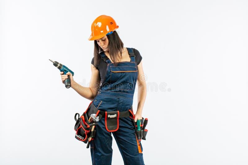 La giovane donna con toolbelt facendo uso di driil ed alcune macchine utensili per lei lavorano a casa Ragazza che lavora al rito immagine stock
