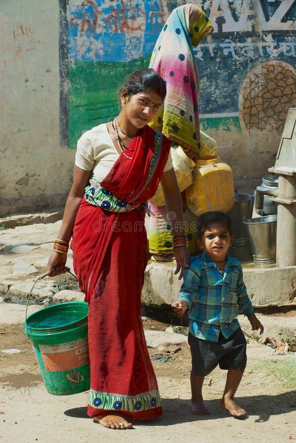 La giovane donna con un bambino porta il secchio di plastica con acqua alla via in Orchha, India fotografia stock libera da diritti