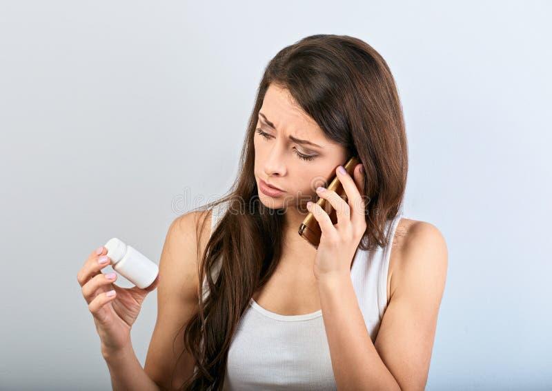 La giovane donna confusa infelice che tiene e che considera la compressa imbottiglia la mano e telefono cellulare rivolgersi per  fotografie stock