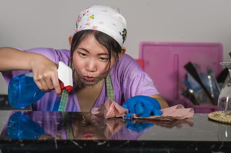 La giovane donna coreana asiatica occupata nei guanti capi di lavaggio e della sciarpa facendo uso di lavaggio delle bottiglie de fotografie stock