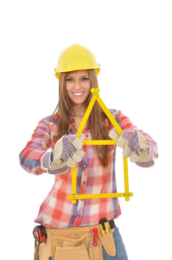 La giovane donna costruisce la casa da una regola di piegatura immagine stock