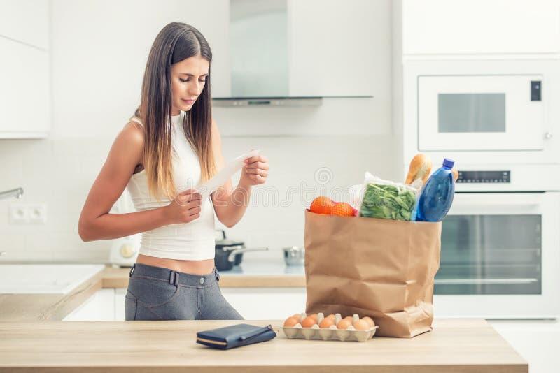 La giovane donna in cucina domestica controlla la fattura Acquisto su una tavola in un sacco di carta immagini stock