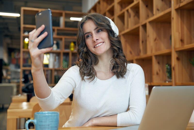 La giovane donna dai capelli lunghi sorridente amichevole in un rivestimento bianco fa fotografia stock libera da diritti