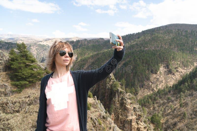 La giovane donna dei pantaloni a vita bassa fa un selfie sulla cima della catena montuosa stupefacente della scogliera abbellire  immagine stock