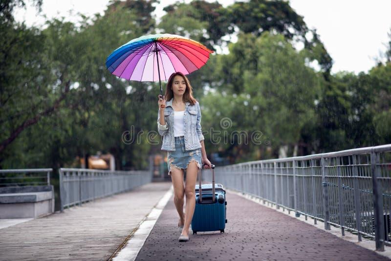 La giovane donna dell'Asia del viaggiatore che cammina sulla via e sparsa la u fotografie stock libere da diritti