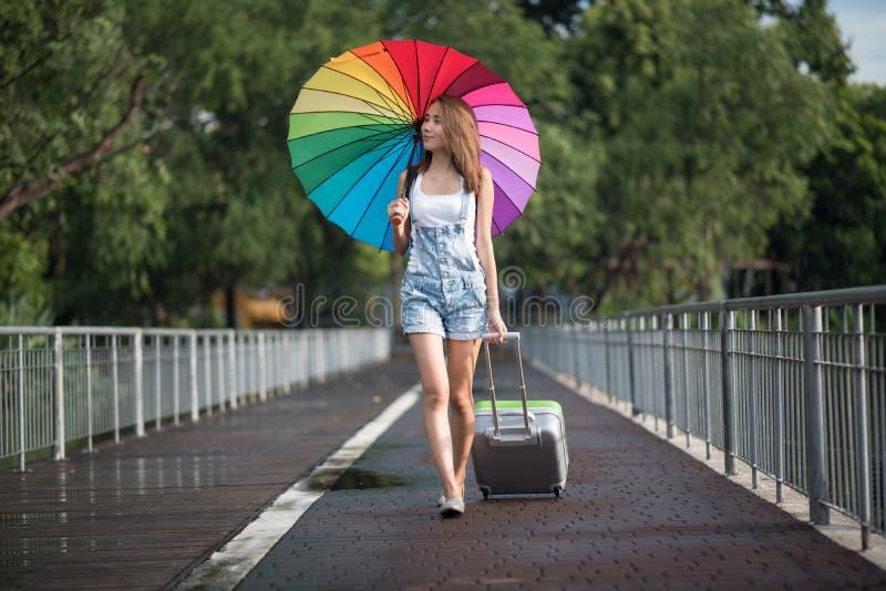 La giovane donna dell'Asia del viaggiatore che cammina sulla via e sparsa la u immagini stock
