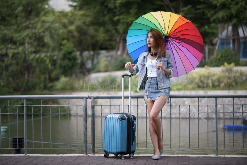 La giovane donna dell'Asia del viaggiatore che sta sulla via con la valigia a immagine stock