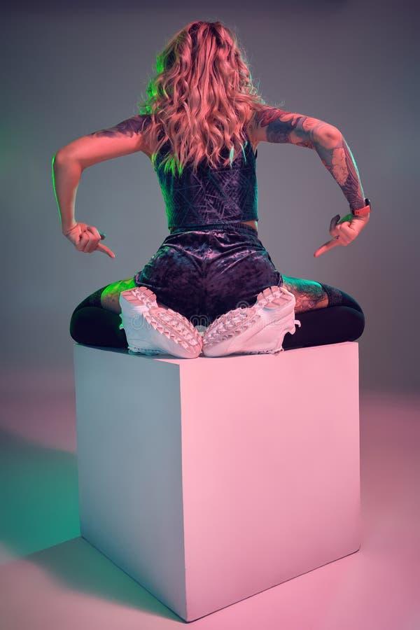 La giovane donna della bionda di forma fisica che indossa il bottino blu del velluto mette la posa in cortocircuito sulla macchin immagini stock