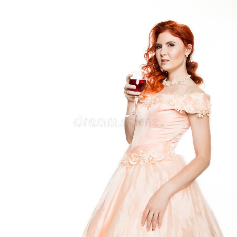 La giovane donna della testarossa beve un vino rosso con un fronte felice e sorridere con un sorriso sicuro Priorità bassa bianca immagine stock libera da diritti