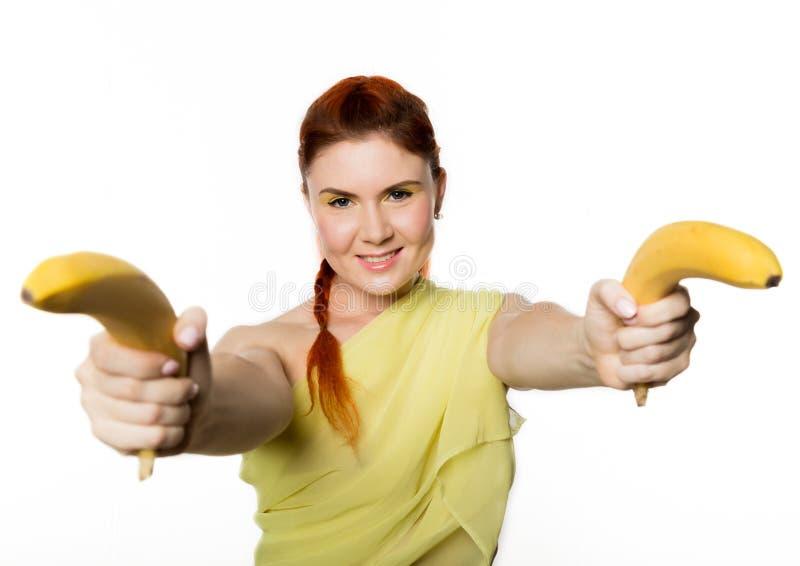 La giovane donna della testarossa che tiene la banana due gradisce la pistola su un fondo bianco immagini stock libere da diritti