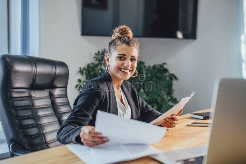 La giovane donna di affari è una buona ragazza seria che lavora nell'ufficio Durante il questo, controlla i documenti esaminandol immagine stock