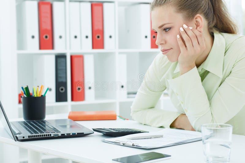 La giovane donna di affari annoiata si siede al suo scrittorio ed esamina lo schermo di computer Concetto occupato di programma fotografie stock libere da diritti