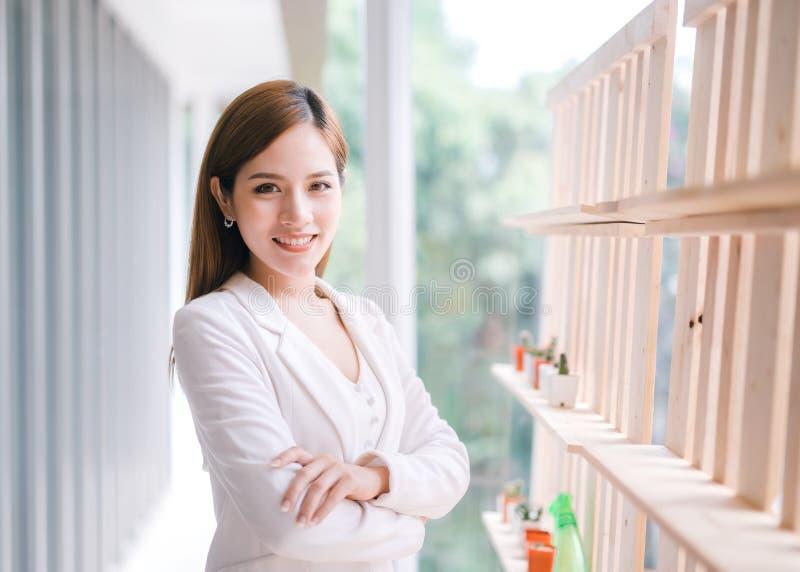 La giovane donna di affari asiatica sorridente con le armi ha attraversato fotografia stock