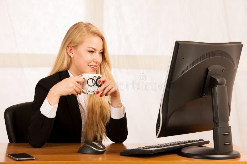 La giovane donna di affari beve il coffe di mattina il suo ufficio de fotografie stock