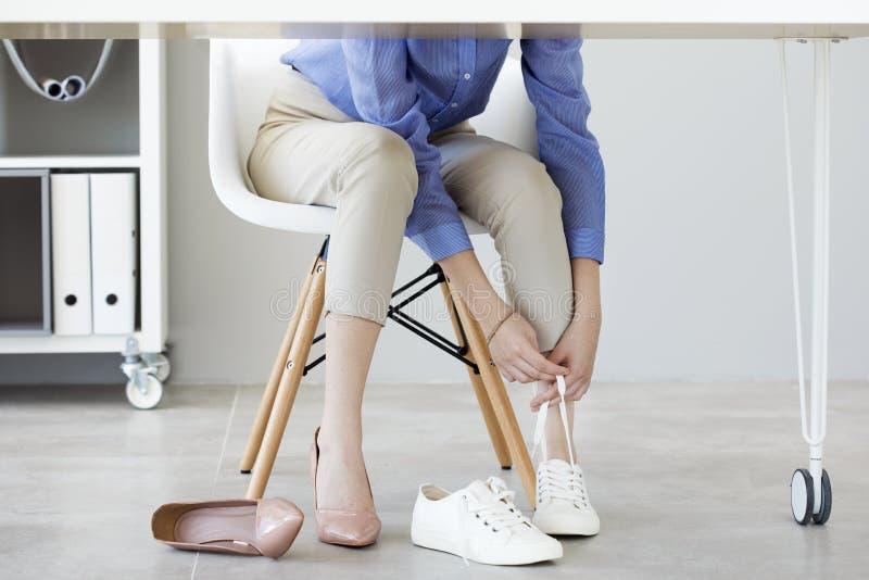 La giovane donna di affari cambia le sue scarpe dovute affaticare fotografie stock libere da diritti