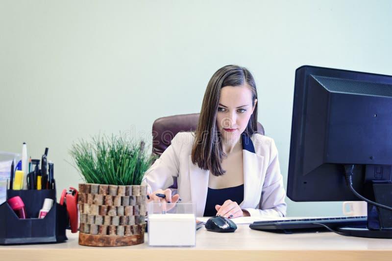La giovane donna di affari che lavora duro sopra lo scrittorio nello studio, rendicontazione finanziaria del ragioniere dell'econ immagini stock libere da diritti