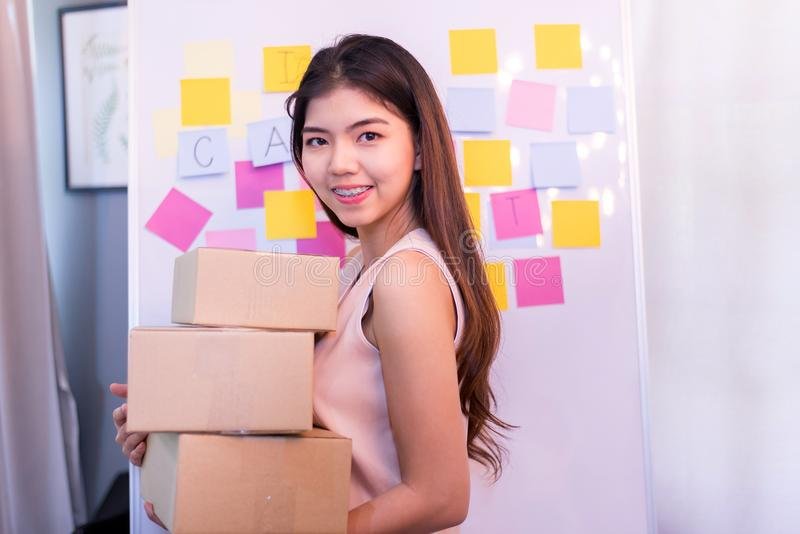 La giovane donna di affari che tiene un pacchetto per preparare la consegna, inizia il piccolo imprenditore fotografia stock