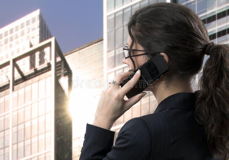 La giovane donna di affari comunica sul mobile fotografie stock