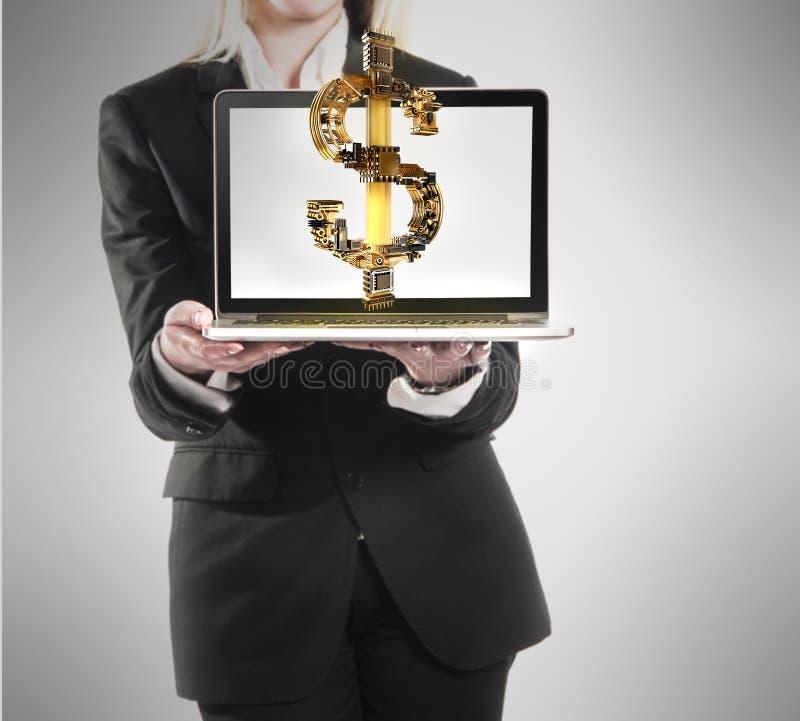 La giovane donna di affari con il computer portatile ed i soldi del dollaro firmano a disposizione immagini stock