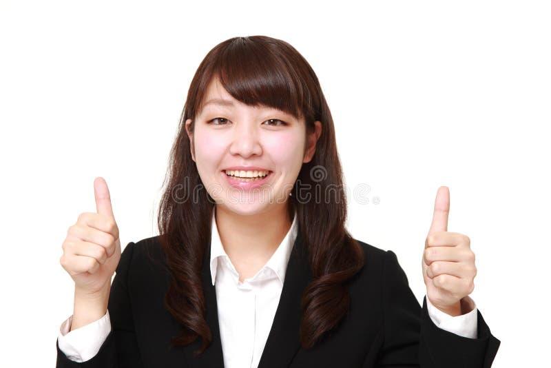 La giovane donna di affari giapponese con i pollici aumenta il gesto immagine stock libera da diritti