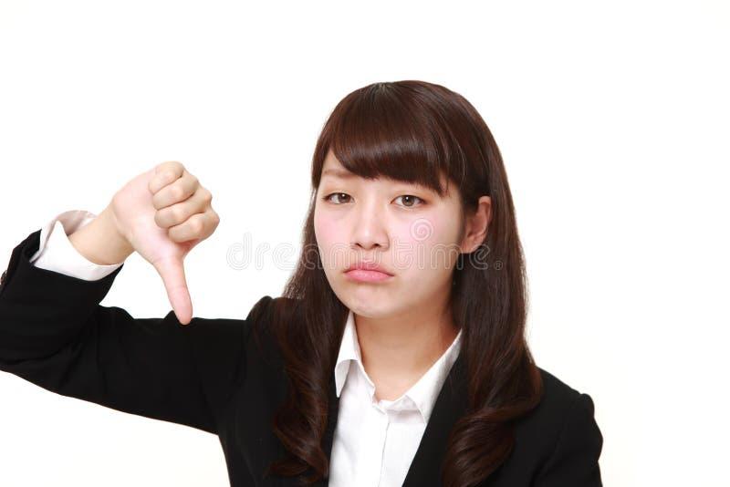 La giovane donna di affari giapponese con i pollici giù gesture fotografia stock