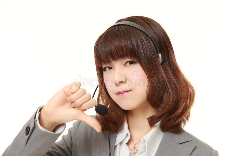 La giovane donna di affari giapponese con i pollici giù gesture fotografia stock libera da diritti