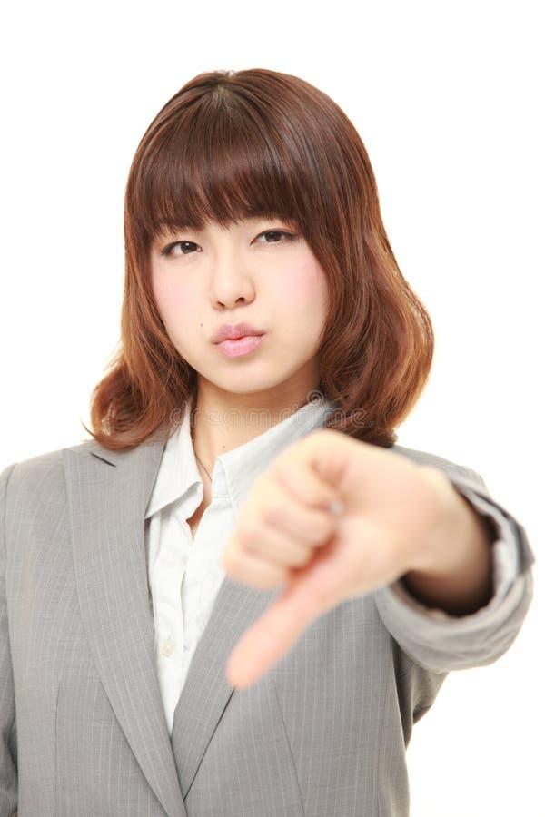 La giovane donna di affari giapponese con i pollici giù gesture immagine stock libera da diritti