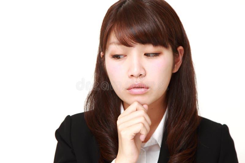 La giovane donna di affari giapponese si preoccupa per qualcosa immagine stock